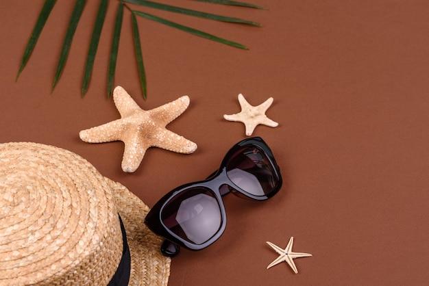 Óculos de sol e chapéu com estrelas do mar em uma superfície colorida