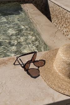 Óculos de sol e chapéu de palha ao lado da piscina de mármore com água azul clara com reflexos de sombra de luz solar de ondas