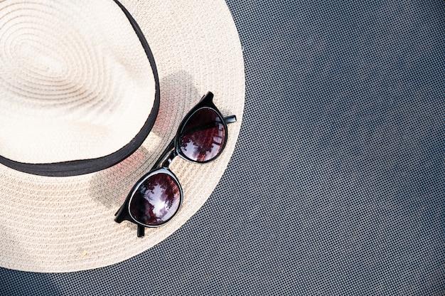 Óculos de sol e chapéu de palha na cama de praia