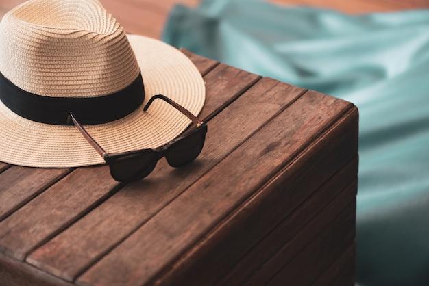 Óculos de sol e chapéu de palha no assoalho de madeira na praia, conceito do verão.
