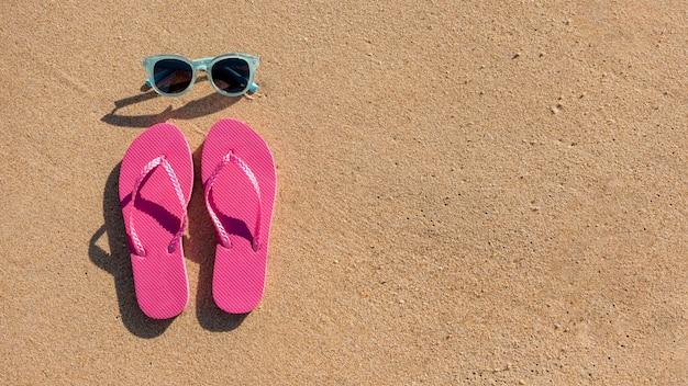 Óculos de sol e chinelos de praia na areia