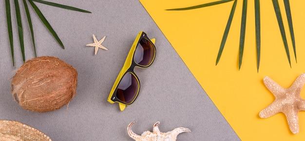 Óculos de sol e coco com conchas e estrelas do mar em uma superfície colorida
