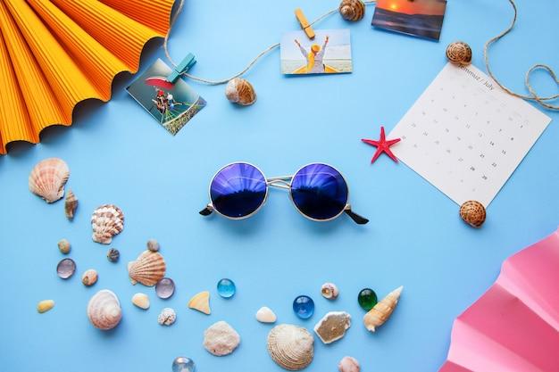 Óculos de sol e conchas do mar sobre o fundo azul flat lay