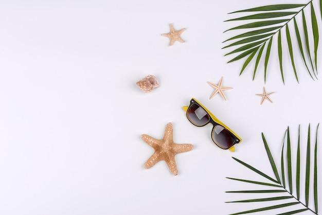Óculos de sol e estrelas do mar em um fundo branco. fundo de verão