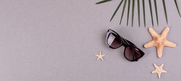 Óculos de sol e estrelas do mar em uma superfície colorida