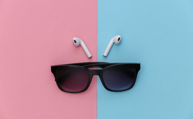 Óculos de sol e fones de ouvido sem fio em fundo rosa pastel azul.
