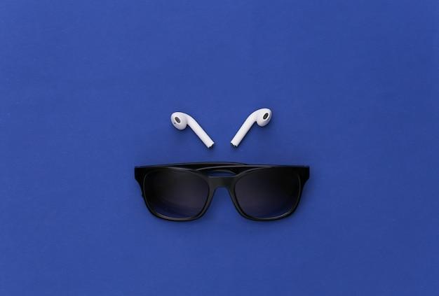 Óculos de sol e fones de ouvido sem fio no fundo azul clássico.