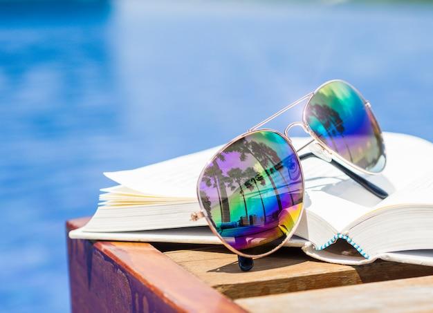Óculos de sol e livro ao lado da piscina. férias, conceito de verão