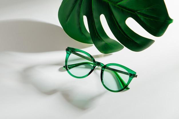 Óculos de sol elegantes com luz solar intensa com folha tropical. conceito de férias de verão.