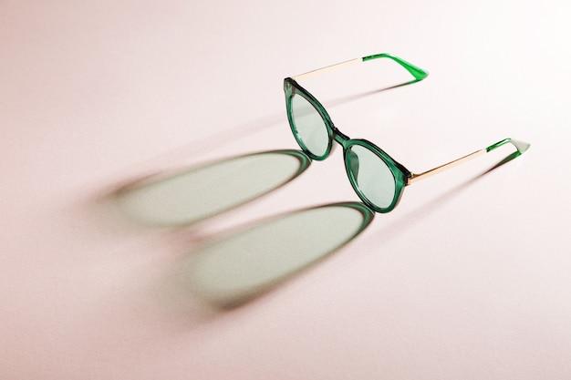 Óculos de sol elegantes com luz solar intensa sobre fundo rosa. . conceito de férias de verão.