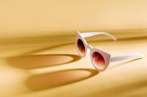 Óculos de sol elegantes em fundo amarelo. . conceito de férias de verão.