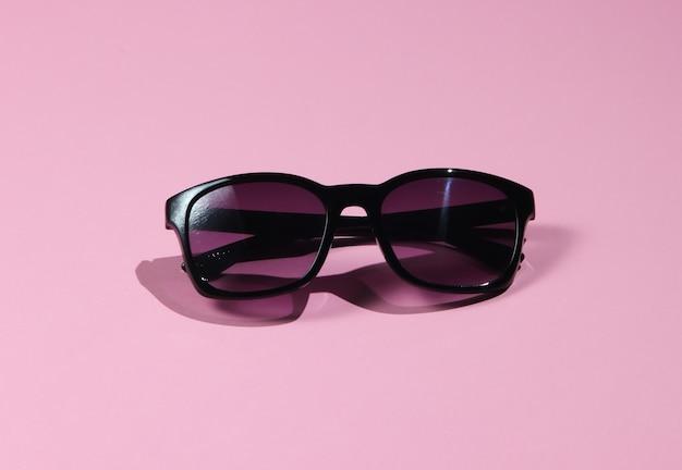 Óculos de sol elegantes em um fundo rosa pastel. moda disparada com sombras.