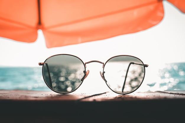 Óculos de sol em cima da mesa à beira-mar em férias relaxantes. férias de verão e conceito de viagens