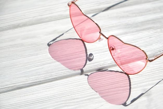 Óculos de sol em forma de coração na mesa de madeira branca