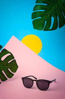 Óculos de sol em um fundo tropical colorido