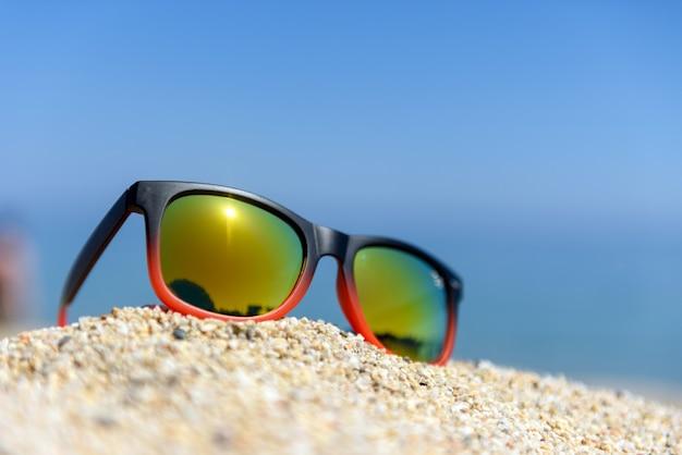 Óculos de sol espelhados fecham-se na areia da praia com o reflexo do mar