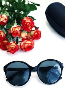 Óculos de sol feminino em fundo branco com rosas e estojo. loja de óptica, proteja seus olhos da luz uv.