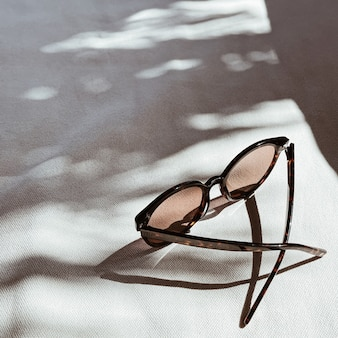 Óculos de sol femininos em fundo branco com sombras desfocadas de luz solar