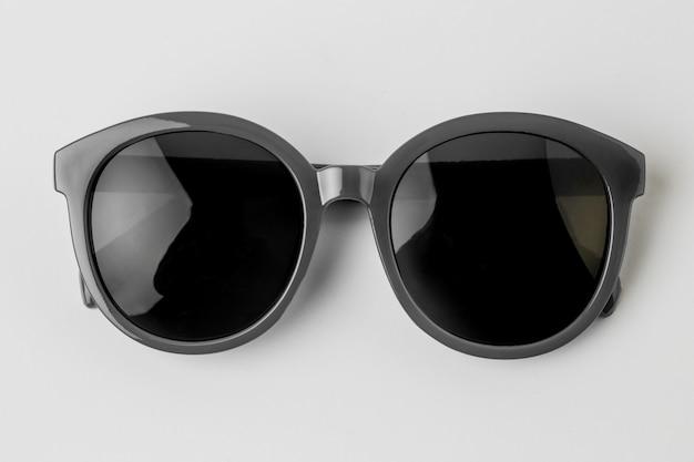 Óculos de sol frescos isolados no fundo branco, vista superior.