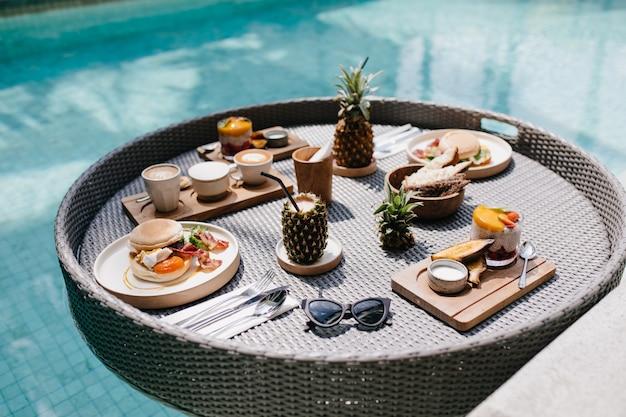 Óculos de sol, hambúrgueres e suco. mesa com almoço exótico na piscina.
