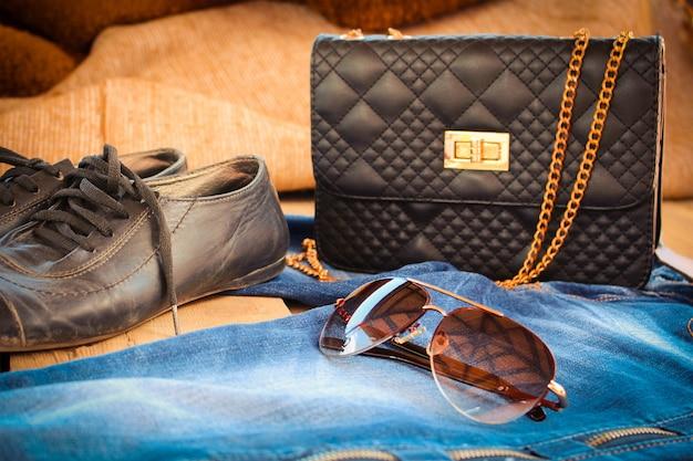 Óculos de sol, jeans, bolsa e sapatos velhos. imagem enfraquecida.