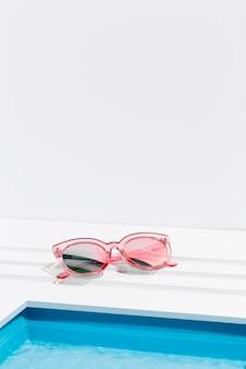 Óculos de sol junto à pequena piscina