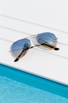 Óculos de sol legais ao lado da pequena piscina