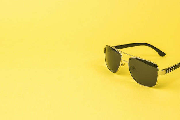 Óculos de sol masculinos para proteção solar em um fundo amarelo. um acessório masculino da moda.