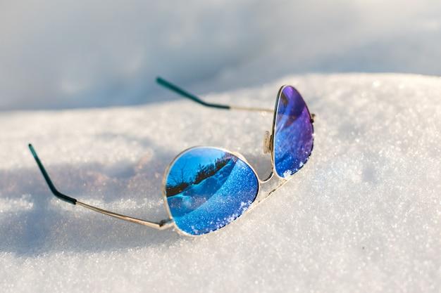 Óculos de sol mentem sobre a neve fofa branca em um dia ensolarado, close-up, plano de fundo, dia de inverno