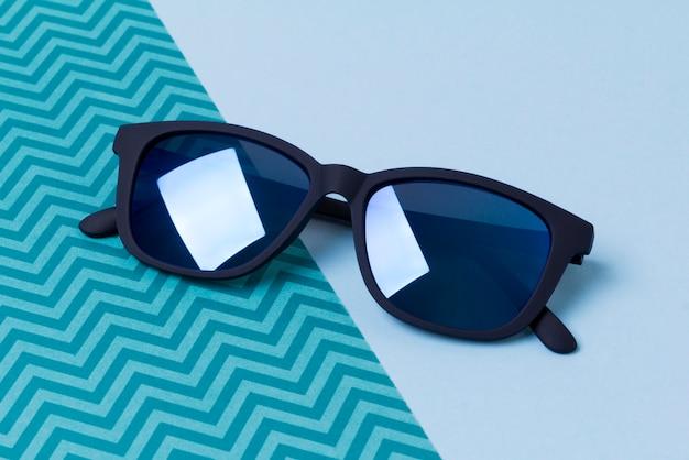 Óculos de sol modernos na moda na mesa criativa azul