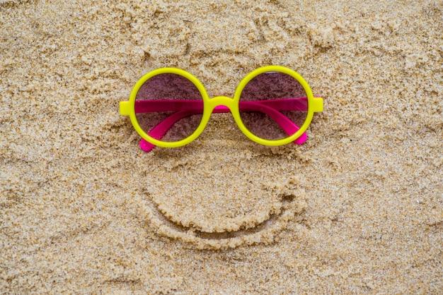 Óculos de sol na areia na praia