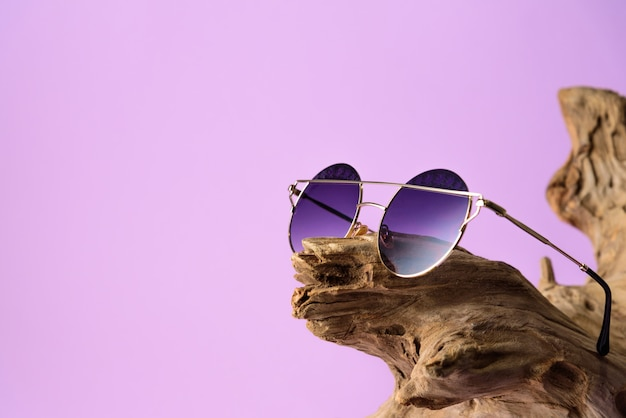 Óculos de sol na moda com lentes roxas colocadas em madeira. em fundo roxo