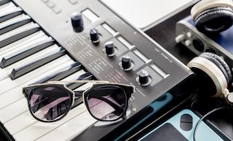 Óculos de sol na moda no teclado de música no estúdio