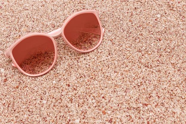 Óculos de sol na praia arenosa com espaço da cópia