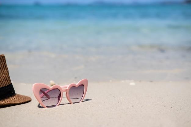 Óculos de sol na praia tropical arenosa branca, férias de verão e conceito de viagem