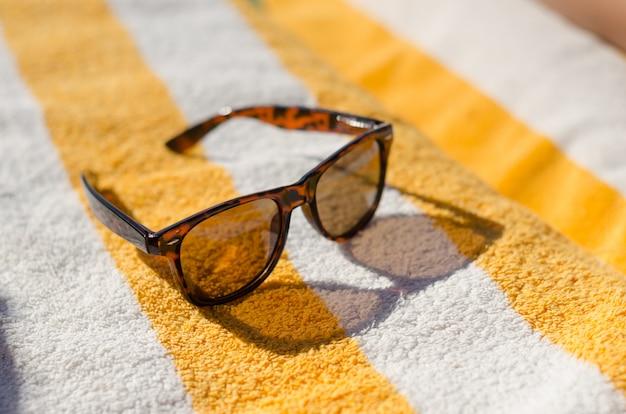 Óculos de sol na toalha de praia amarela