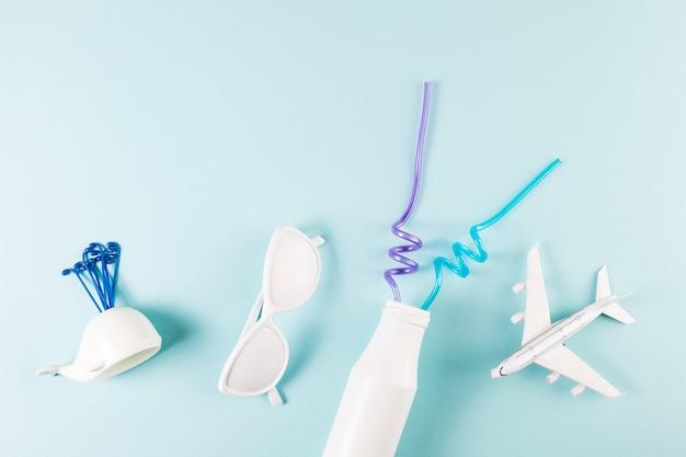 Óculos de sol ornamentais perto de avião de brinquedo com baleia e garrafa com canudos