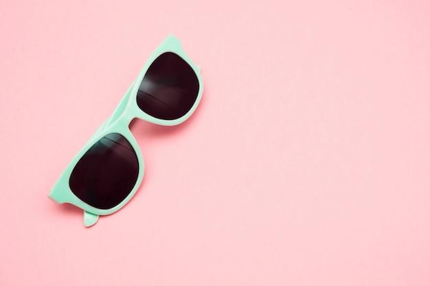 Óculos de sol pasteis verdes isolados na vista cor-de-rosa, superior punchy. conceito de verão.