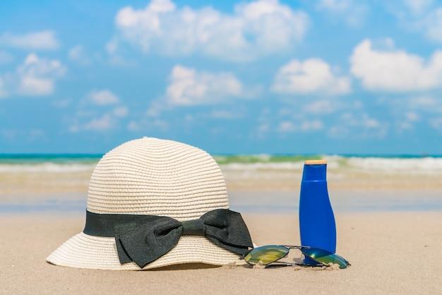 Óculos de sol, protetor solar e chapéu na praia de areia branca