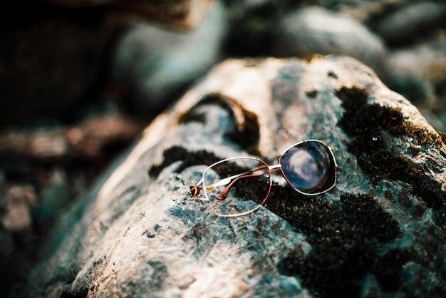 Óculos de sol quebrados na pedra com musgo na luz solar. coisa perdida na pedra musgosa em dia ensolarado. brilho na coisa brilhante. um absurdo aconteceu. óculos de sol perdidos em close-up de pedra. as coisas quebram, a vida continua.