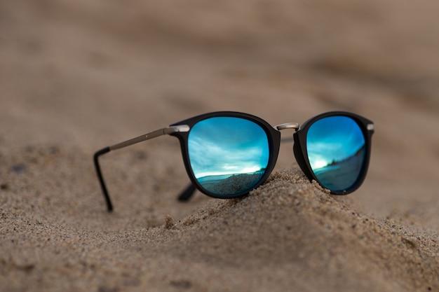 Óculos de sol redondos com reflexo do espelho na areia na praia ensolarada de verão. conceito de férias de viagens.