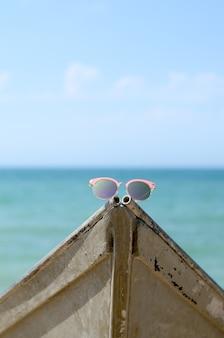 Óculos de sol rosa contra o sol em um barco perto do mar