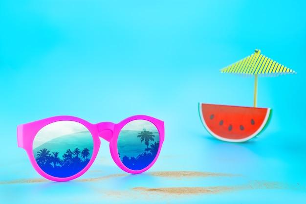 Óculos de sol rosa reflexo do guarda-chuva de areia de árvore de palma