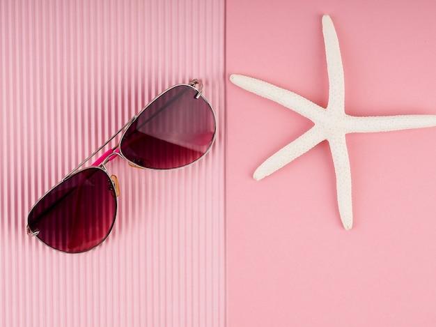Óculos de sol rosa sobre fundo rosa, conceito de férias, cartão postal, verão e viagens.