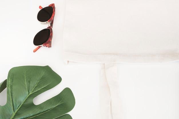 Óculos de sol, saco de pano branco e folha de monstera no fundo branco