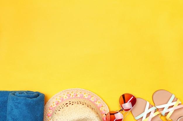 Óculos de sol, toalha, chapéu e sandálias.