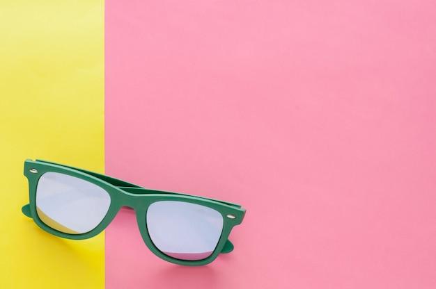 Óculos de sol verdes isolados no fundo colorido por horas de verão.