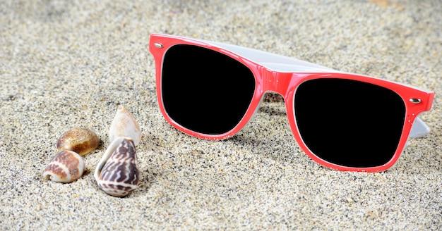 Óculos de sol vermelhos na areia