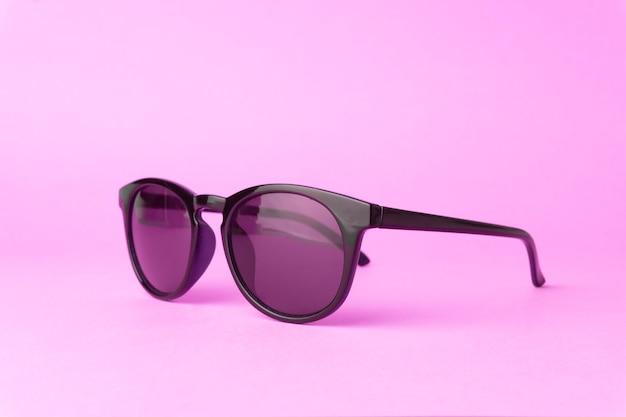 Óculos de sol vintage rosa sobre fundo rosa