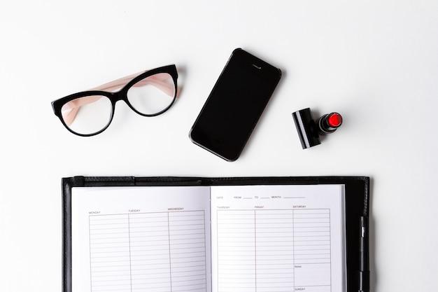 Óculos de telefone batom vermelho e caderno sobre a superfície branca acima.